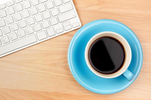 Café preto no copo azul na mesa de madeira marrom