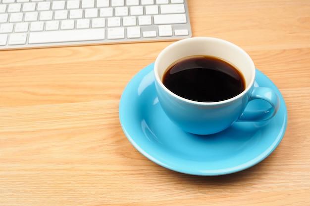 Café preto no copo azul no fundo da mesa de madeira marrom