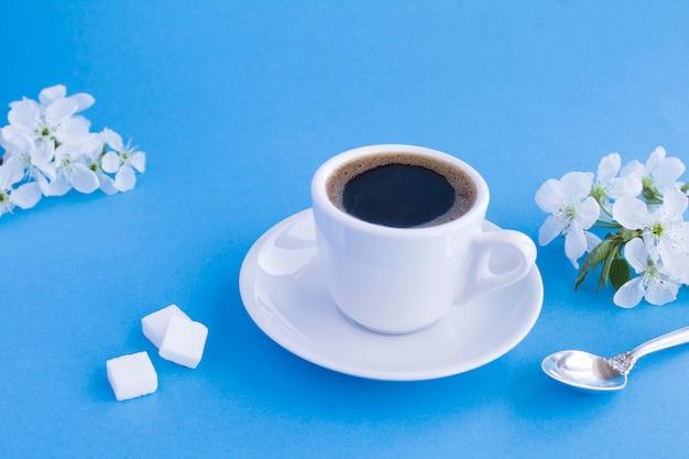 Café preto no copo branco e galhos de árvores floridas