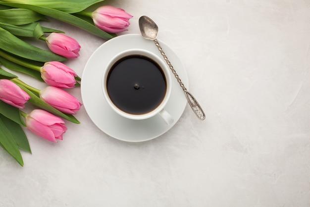 Café preto no copo e nas tulipas brancos.