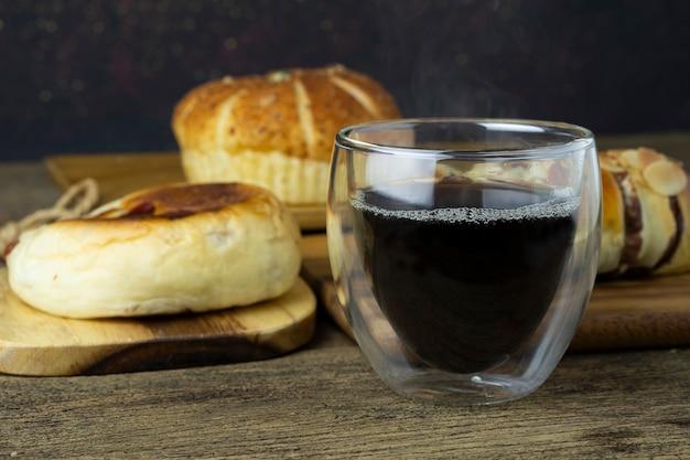 Café preto quente é colocado na mesa de madeira com pão no fundo.