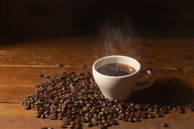 Café preto quente na xícara com café em grão.