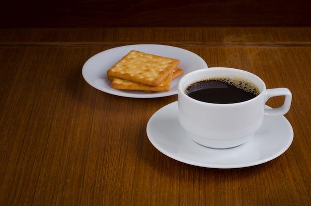 Café preto quente no copo cerâmico branco no saucer sobre o fundo de madeira escuro do teak