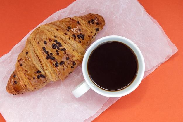 Café preto sem leite em uma xícara branca e um croissant de chocolate em pergaminho e fundo brilhante. café da manhã francês com bolos frescos. vista superior plana com espaço de cópia para o seu texto.