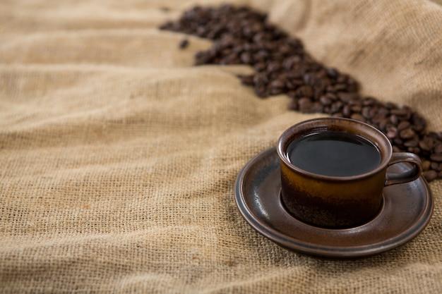 Café preto servido e grãos de café no saco