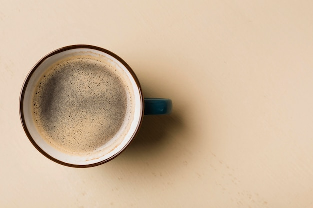 Café preto sobre fundo bege com espaço de cópia