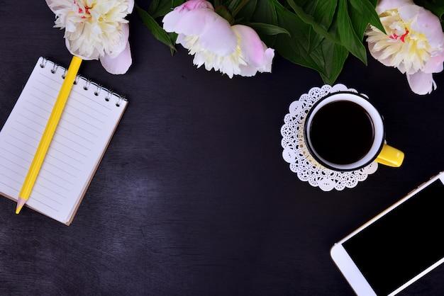 Café preto, telefone móvel em um fundo preto de madeira