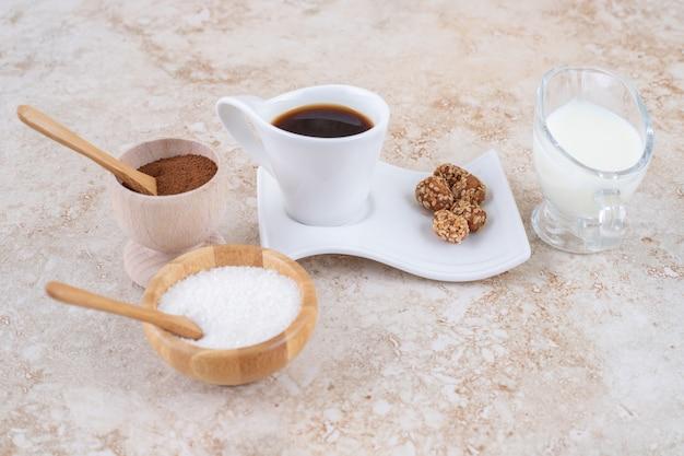 Café preto, tigelas de pó de café moído e açúcar e amendoim glaceado