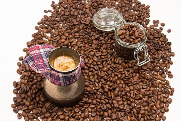 Café pronto com espuma na cafeteira. grãos de café torrados em frasco de vidro. grãos de café na mesa. fundo branco.