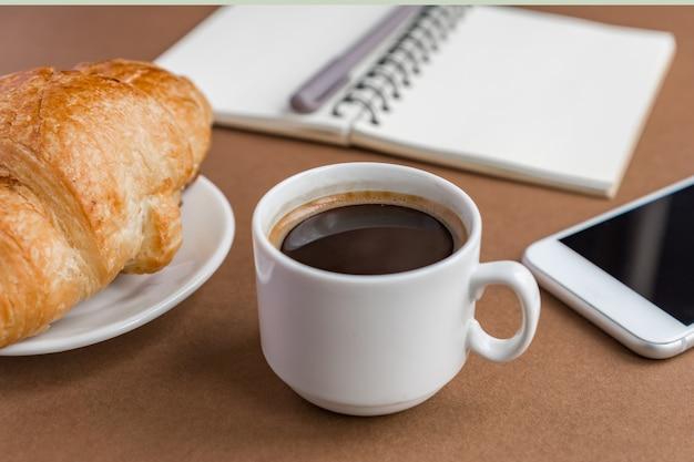 Café quebrar com croissant e expresso. freelancer no trabalho.