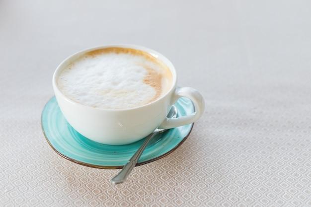 Café quente cappuccino latte art em copo de cor jade isolado em uma mesa bege. vista superior da xícara de café appuccino. latte art em espuma leitosa.