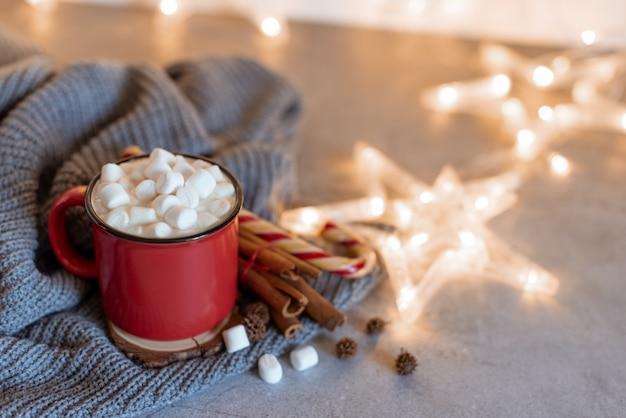 Café quente chantilly de creme de inverno em uma caneca vermelha com biscoitos em forma de estrela e cachecol quente - vida rural ainda