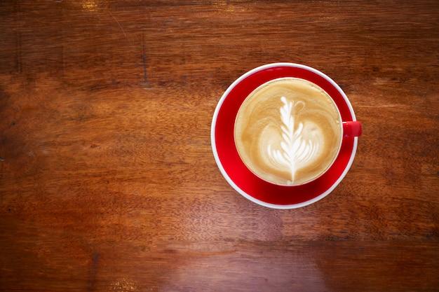 Café quente com arte no final do copo vermelho. bebida favorita para o amante de cafeína.