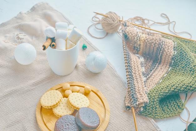 Café quente com biscoitos, marshmallows, canela, decorações de natal e cachecol tricô