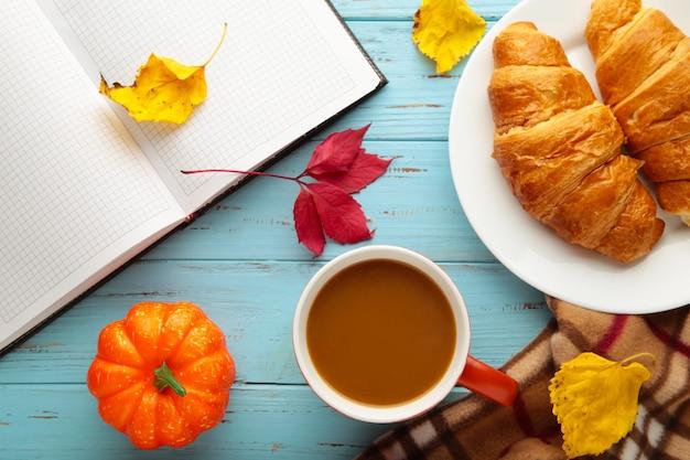Café quente com croissant e folhas de outono em azul - conceito de relaxamento sazonal. vista do topo