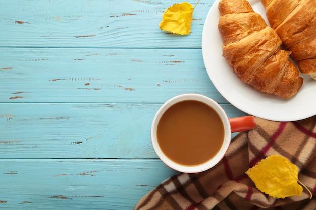 Café quente com croissant e folhas de outono em azul - conceito de relaxamento sazonal