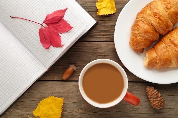 Café quente com croissant e folhas de outono em cinza - conceito de relaxamento sazonal. vista do topo