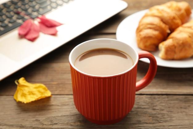 Café quente com croissant e folhas de outono em cinza - conceito de relaxamento sazonal.