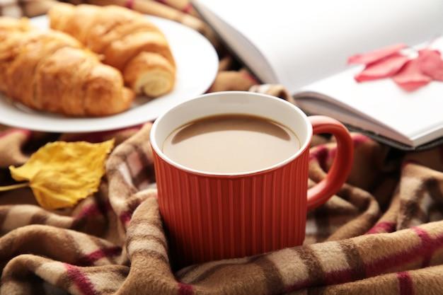 Café quente com croissant e folhas de outono em xadrez - conceito de relaxamento sazonal