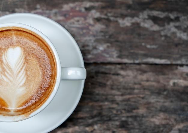 Café quente com latte art na mesa de madeira