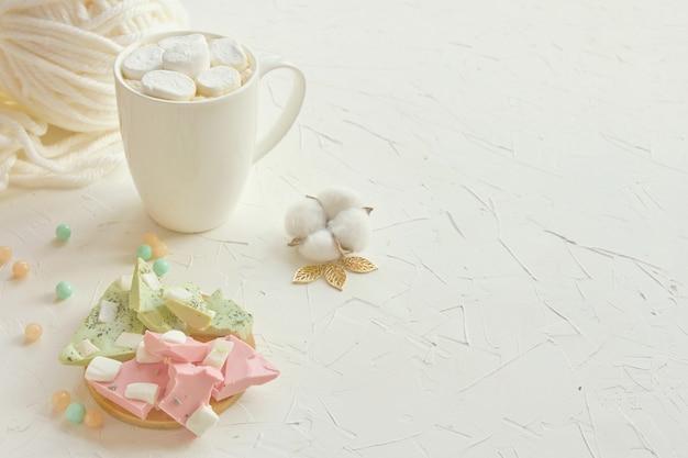 Café quente com marshmallow em uma caneca branca ao lado de limão e morango chocolate