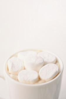 Café quente com marshmallow em uma caneca branca em cima da mesa. safra vertical