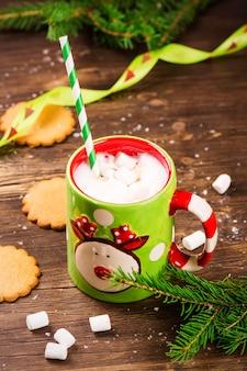 Café quente com marshmallows e biscoitos de gengibre no fundo rústico de madeira. cartão de natal.