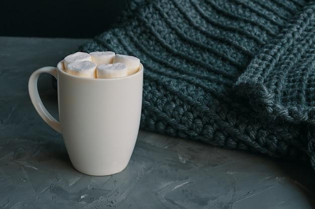 Café quente com marshmallows em uma caneca branca na mesa ao lado de um cobertor quente