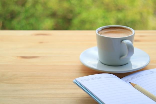Café quente com papel de nota na mesa de madeira