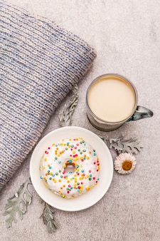Café quente com um donut. bebida de inverno para um bom humor com blusa, folhas e flores.