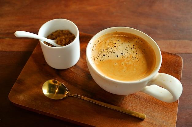 Café quente com um pote de açúcar mascavo e colher de chá de latão na bandeja de madeira