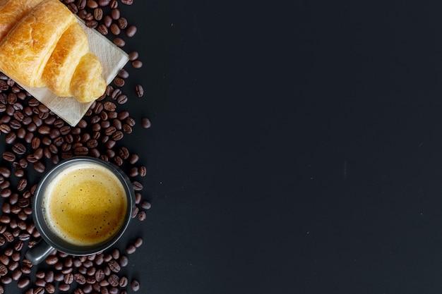 Café quente, croissants de feijão e manteiga na mesa preta