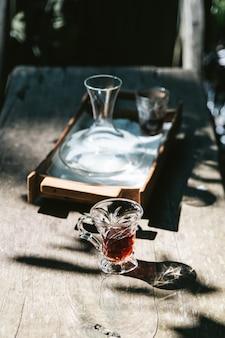 Café quente do gotejamento no vidro bebendo na tabela de madeira com luz solar áspera.