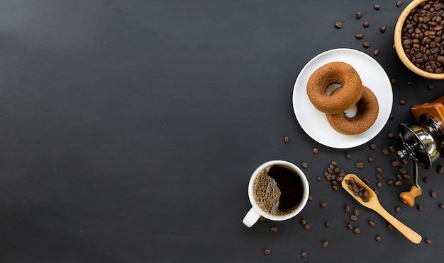 Café quente, donuts, feijão e moedor manual na mesa preta