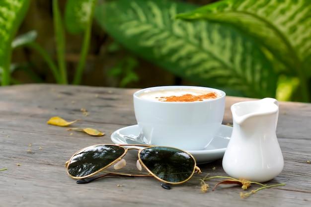 Café quente e chá quente com copos, deitado sobre uma mesa de madeira
