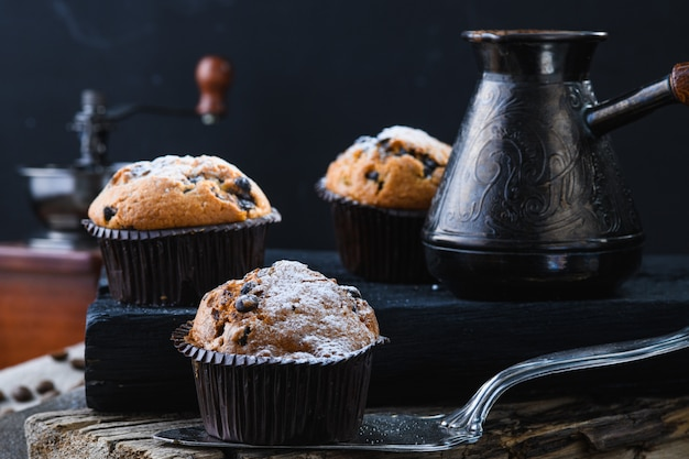 Café quente e cupcakes em pranchas de madeira, estilo rústico