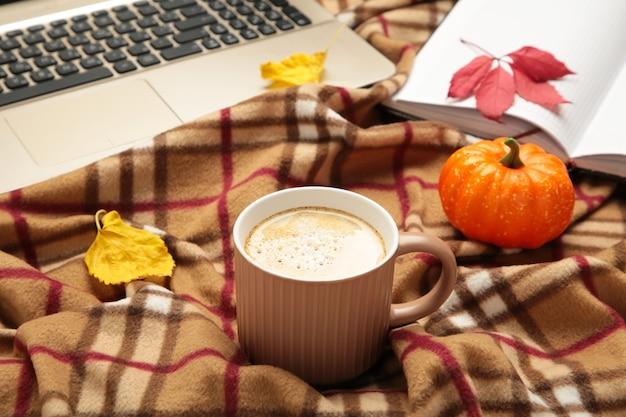 Café quente e folhas de outono com caderno na manta - conceito de relaxamento sazonal. vista do topo