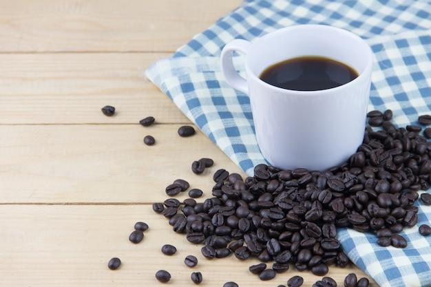 Café quente e grão de café na manta de guardanapo azul e branco Foto Premium