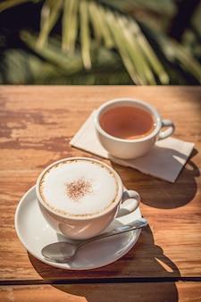 Café quente e lugar de chá quente na mesa de madeira no início da manhã com copyspace