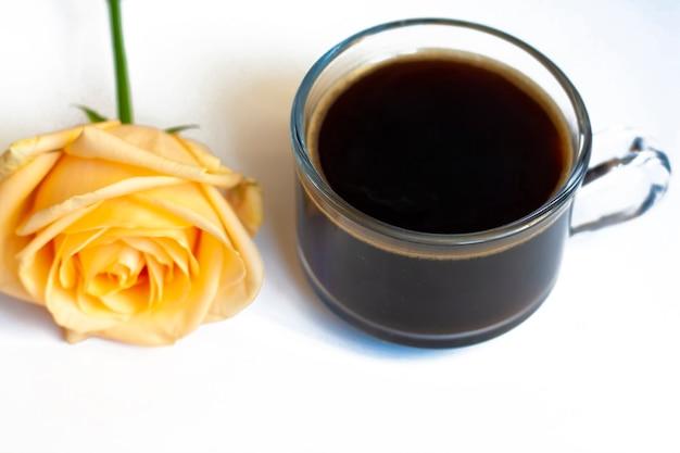 Café quente e uma rosa amarela em um fundo branco
