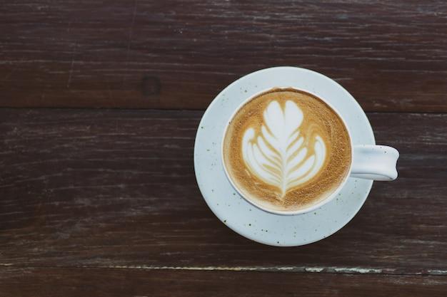 Café quente em copo branco na mesa de madeira