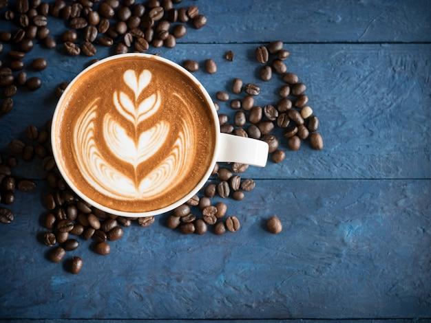 Café quente em um copo com arte bonita do latte do leite da espuma e feijões de café no fundo de madeira azul da tabela. o cappuccino ou o latte com espuma da espuma, bebem o conceito.