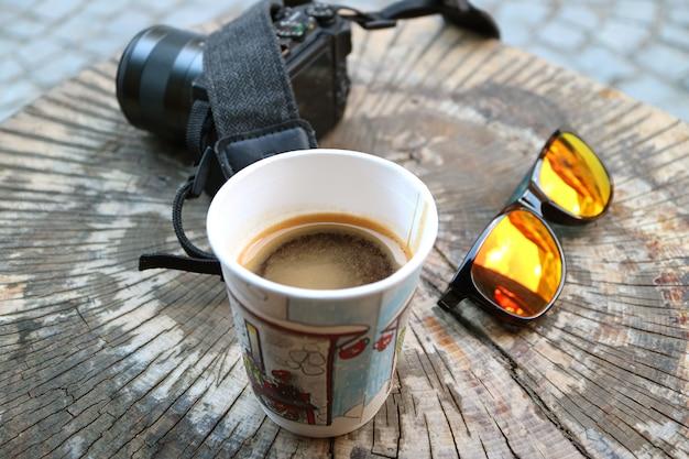 Café quente em um copo de papel na mesa de tronco de árvore com câmera e óculos de sol