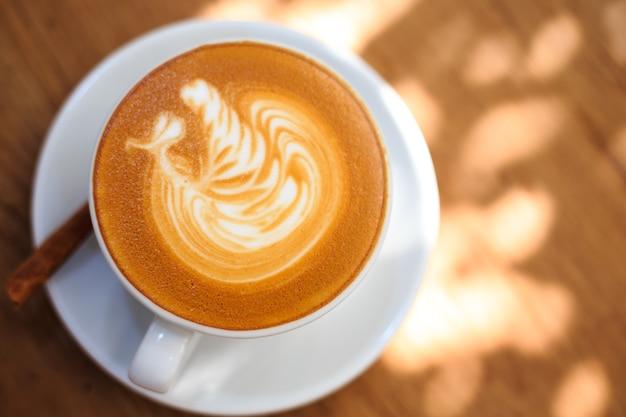 Café quente em um copo em um assoalho de madeira