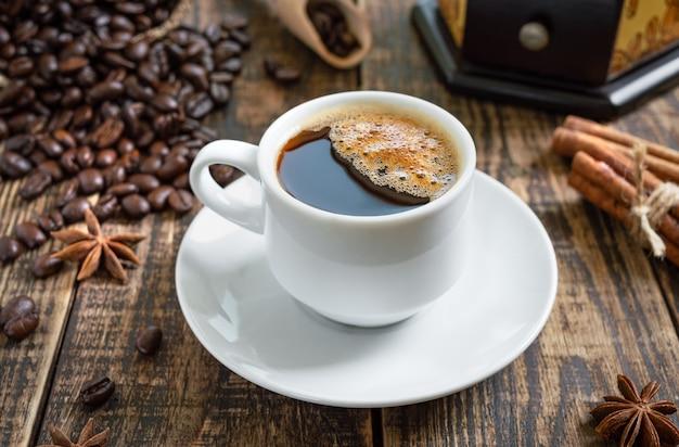 Café quente em um fundo de madeira com grãos de café, moedor de café manual, paus de canela.