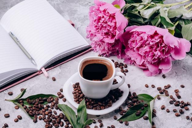 Café quente em uma tigela e peônias flores