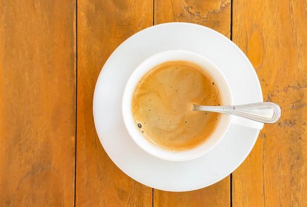 Café quente em uma xícara branca com pires em uma mesa de madeira