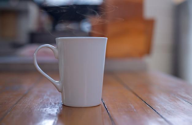 Café quente em uma xícara branca em cima da mesa