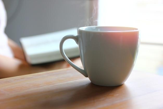 Café quente em xícara de cerâmica branca na mesa de madeira com mulher lendo livro de fundo à luz da manhã