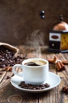 Café quente fumegante em uma velha mesa de madeira com grãos de café, moedor de café manual. visão vertical